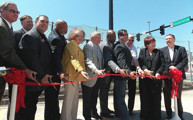 Officials cut a ribbon Tuesday, signaling the final completion of the diverging-diamond bridge on Pleasant Hill Road at Interstate 85. Those cutting the ribbon, from left to right, are: Joe Allen of the Gwinnett Place CID, Todd Long of the Georgia Department of Transportation, state Rep. Pedro Marin, state Rep. Dewey McClain, Commissioner Lynette Howard, State Transportation Board member Rudy Bowen, State Road and Tollway Director Chris Tomlinson, Gwinnett Place CID board member Mark Williams, David Snell of E.R. Snell Contractor, Commission Chairwoman Charlotte Nash and Commissioner Jace Brooks. (Staff Photo: Camie Young)